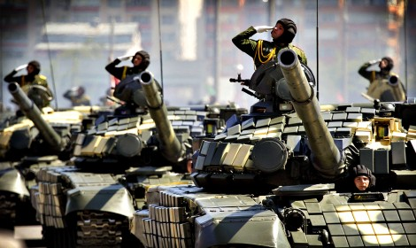 Belarussian servicemen salute from tanks, as they take part in a